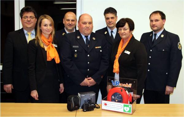 Das Bild zeigt die Übergabe des Defibrillators und der Digitalkamera