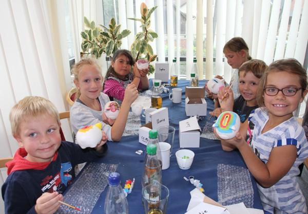 Kinder des Kathi-Baur-Horts bemalen Sparschweine